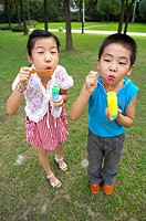 Two children standing on the lawn and blowing bubbles