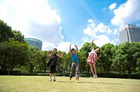 Three children jumping in mid_air with arms outstretched