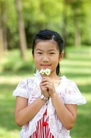 Girl smelling flowers and looking at the camera with smile