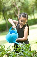 Girl holding watering can and watering on trees, Child