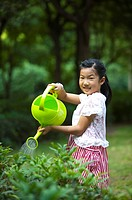 Girl holding watering can and watering with smile, Child