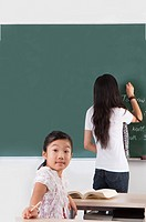 Child, Girl looking over shoulder with teacher standing and writing