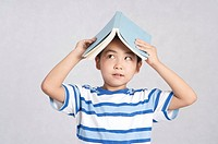 Child, Boy holding book on head and looking up