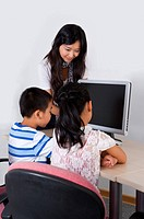 Child, Young teacher teaching and looking at the computer with children