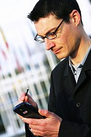 DEU Germany : Man is working with a PDA pocket-computer. |