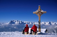 Two persons sledging at cross of Bischlinghoehe, view to Hochkoenig range, skiing area Werfenweng, Salzburg, Austria
