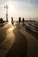 People at the at the seaside promenade at sunset, Lazise, Lake Garda, Italy, Europe