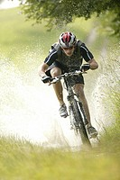 Mountainbiker riding through a puddle of water, Garmisch_Partenkirchen, Upper Bavaria, Bavaria, Germany