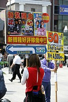 JPN, Japan, Tokyo: People holding advertising poster, entrance of Shimbashi station