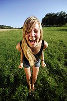 young girl standing on a meadow, screaming