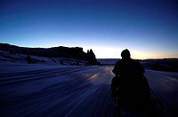 Man on a skidoo in the evening light, Seiser Alm, Schlern, South Tyrol, Italy