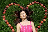 A woman lying inside a heart of fruit on a meadow, South Tyrol, Italy, Europe