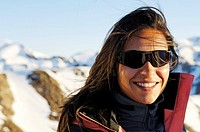 Smiling woman wearing sunglasses in front of snowy mountains, Schnals valley, Val Venosta, South Tyrol, Italy, Europe