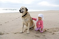 A 1 year old girl stroking a dog on the beach, Anatolien Shepherd, Punta Conejo, Baja California Sur, Mexico