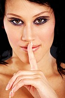 young woman with eye_catching eye make_up laying a forefinger on her mouth, smirking