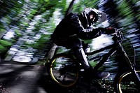 Mountainbiker rideing his bike in the forest, Dillingen, Bavaria, Germany