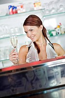 young barmaid behind the bar raising a glass of sparkling wine with a smile