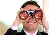 businessman looking through binoculars with a smile