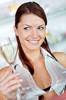 smiling young woman festively dressed with full glass of sparkling wine