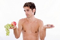 man with naked upper body deliberatively looking at fruits in one and pills in the other hand