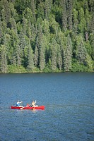 Family paddles a canoe together on Byers Lake, Summer, Denali State Park, Southcentral Alaska