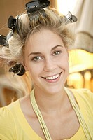 Blonde model with curlers smiling into the camera