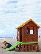little boy during cold weather playing in the sand beside a toy house with slide, Netherlands, North Sea, Noordwijk