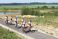 Bikers cycling along mud flats and creek in nature reserve Putten West, nature development in harbour of Antwerp, Belgium