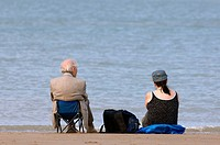 Elderly couple looking at the sea from beach, Belgium
