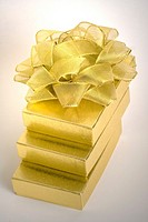 Three stacked gold boxes with a gold bow on the top against a white background  PHOTO-Linda Matlow/PIXINTL
