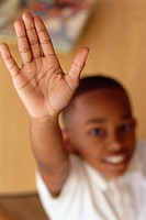Child raising hand in classroom