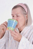 elderly ill woman in bathrobe drinking a cup of tea