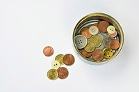 empty tin can with coins and buttons
