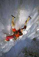 man ice climbing, with helmet, rope and ice axe