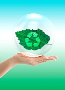 Environmental care, conceptual image. Computer artwork of a hand supporting a glass sphere with a leaf inside and a recycling symbol. This represents ...