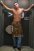 half naked elevator repairer standing in front of a lift