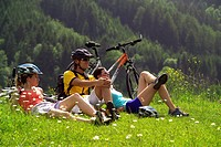 three cyclists have a breather in meadow, Austria, Styria, Schladming