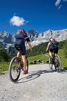 man and woman on mountainbikes in front of an alpine scenery, Austria, Upper Austria, Gmunden