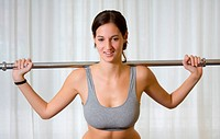 young woman doing exercise with weight bar
