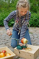 children are making an apple dehydrator, girl is peeling and cutting an apple using an apple peeling machine, Germany