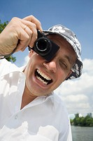 An ecstatic man taking a photo with a digital camera