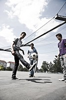 Three boys playing football in a fenced_in football ground