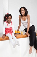 A mother and daughter sitting on a kitchen counter