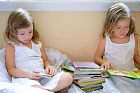 Beautiful twin little girls doing school homework at home