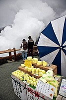 young couple looking at the edge of a volcano and sweet fake sulfur for sale .Nakadake volcano,Aso mountain,Kumamoto,Kyushu,Japan