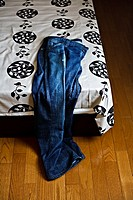 Blue old jeans on a bed and wooden flooring