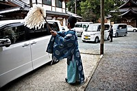 Japanese shintoist priest purificating some new cars in a temple Japan