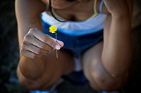 young teenager squatting with a yellow flower in her hand
