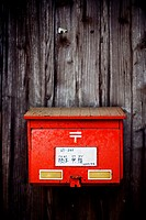 Japanese red mailbox in a wooden old door