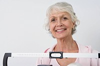 Senior woman stands on hospital scales